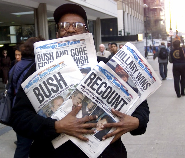 A man holds four copies of the Chicago Sun Times, which each came out on Nov. 8, 2000, the day after the election.