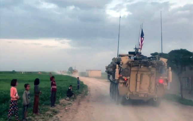 Syrian children wave at U.S. forces in northern Syria.