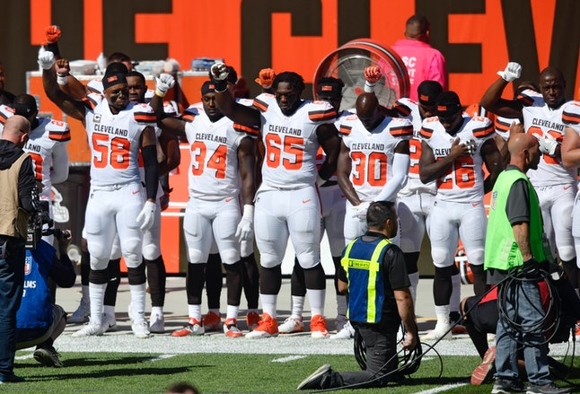 Members of the Cleveland Browns hold their arms up in protest during the national anthem before an NFL football game against the Cincinnati Bengals on Sunday in Cleveland.