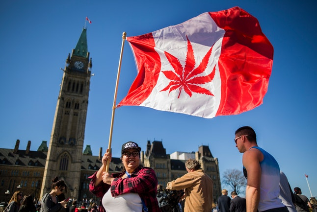 A woman waves a flag with a marijuana leaf on it to celebrate National Marijuana Day in Ottawa, Canada.