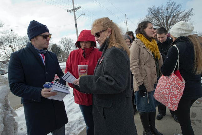 A Trump supporter hands out caucus registration forms in Iowa.