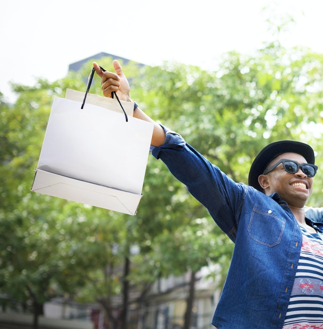 Happy man enjoys deals scored on man goods, as depicted by stock photo.