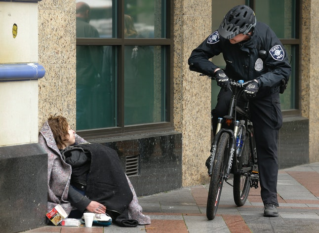 Seattle police Officer Matt Chase, right, talks to a woman sitting under a blanket in a downtown Seattle park, Tuesday, April 7, 2015.