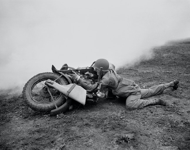 Corporal Francis Rivers, of Cambridge, Mass., uses his motorcycle as a shield while he fires at the enemy during maneuvers in England on Oct. 2, 1942. At the time he was serving as a scout for his unit which was attacked by enemy planes, which dropped smoke bombs and simulated mustard gas.