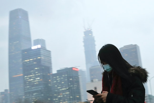 A woman wearing a medical mask looks at her smart phone while walking in Beijing.