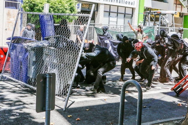 Antifa militants use fencing and trash cans to protect themselves from police as smoke bombs are launched at them and counter protesters on Aug. 5, 2018 in downtown Berkeley, California.