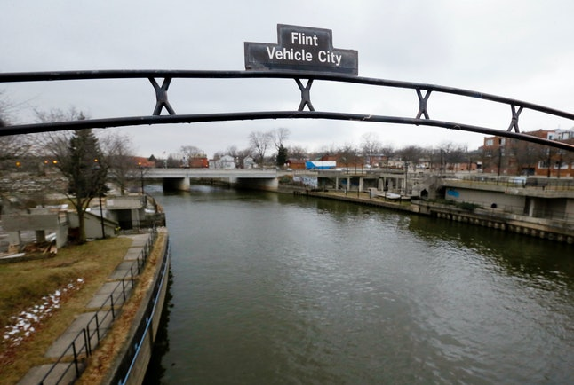 A Jan. 26, 2016, file photo shows a sign over the Flint River in Flint, Michigan.