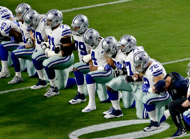 The Dallas Cowboys take a knee prior to the national anthem prior to an NFL football game against the Arizona Cardinals Monday.