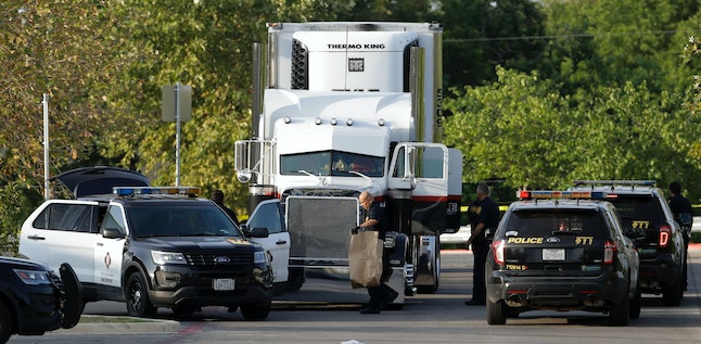 San Antonio police officers investigate the scene where 10 people were found dead in a tractor-trailer loaded with at least 30 people outside a Walmart.