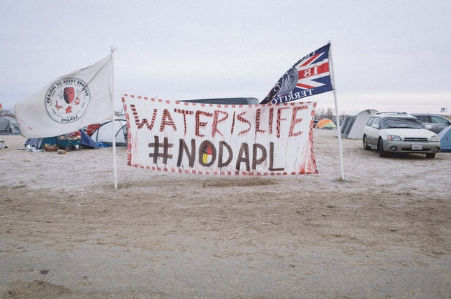 """A banner at the Standing Rock reservation reads """"Water is life #NODAPL."""""""