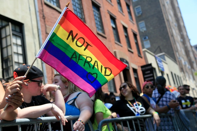 In this June 26, 2016, file photo, an onlooker holds a rainbow flag during the NYC Pride Parade in New York City.