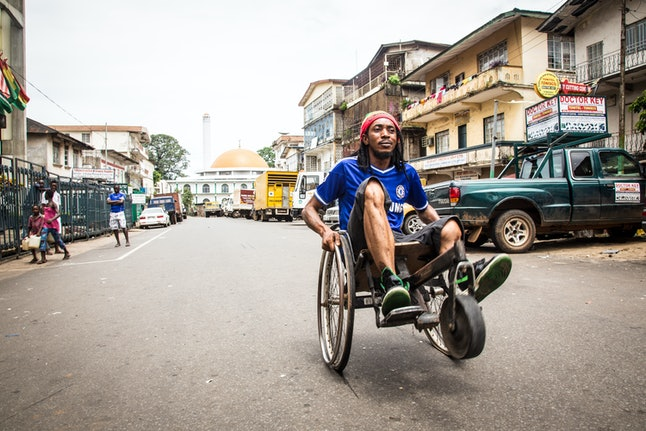 A man travels along a street in his wheelchair during a three-day lockdown to prevent the spread on the Ebola virus in Freetown, Sierra Leone, Sunday, Sept. 21, 2014.