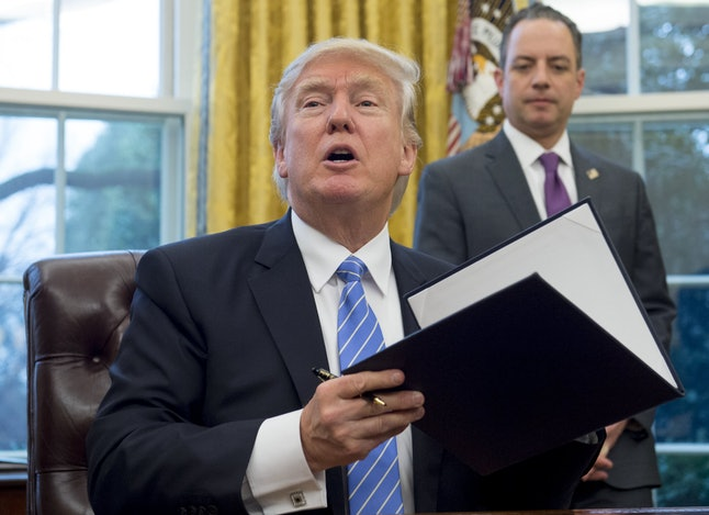 White House Chief of Staff Reince Priebus looks on as President Donald Trump signs an executive order in the Oval Office in January.