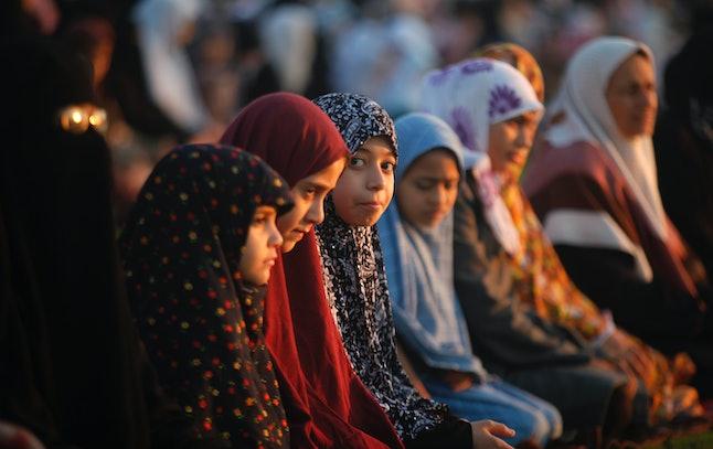 Palestinian girls pray on the first day of Eid al-Adha in Al-Yarmouk stadium in Gaza City.