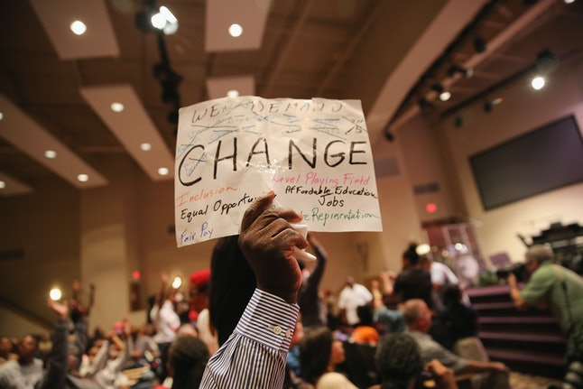 Louis Wilson holds up a sign during the Ferguson city council meeting on September 9, 2014 in Ferguson, Missouri.