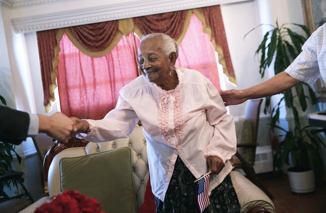 Dominican-born Braulia Fabian, 101, is congratulated after taking the oath of allegiance to the United States at a homebound naturalization service March 18 in New York.