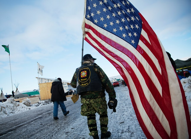 A Navy veteran who came to join the protest against the pipeline holds a flag.
