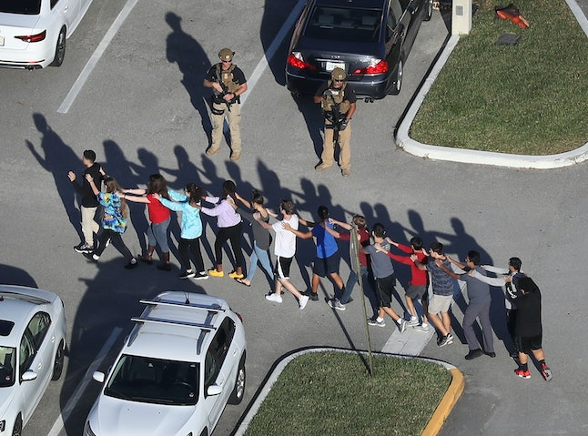 Students are led out of Marjory Stoneman Douglas High School after a former student allegedly killed 17 and wounded more than a dozen others on Wednesday.