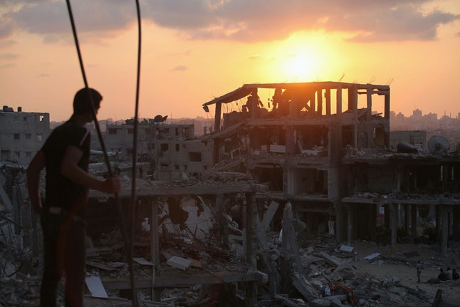 A Palestinian boy stares at the debris of destroyed buildings as Palestinians start to return their homes during ceasefire in al-Shaaf neighborhood Gaza City, Gaza on August 31, 2014.