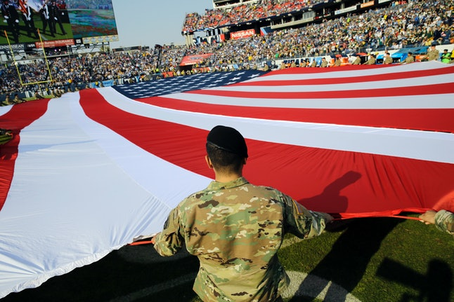 Soldiers hold a large American flag before an NFL football game between the Tennessee Titans and the Green Bay Packers in 2016.