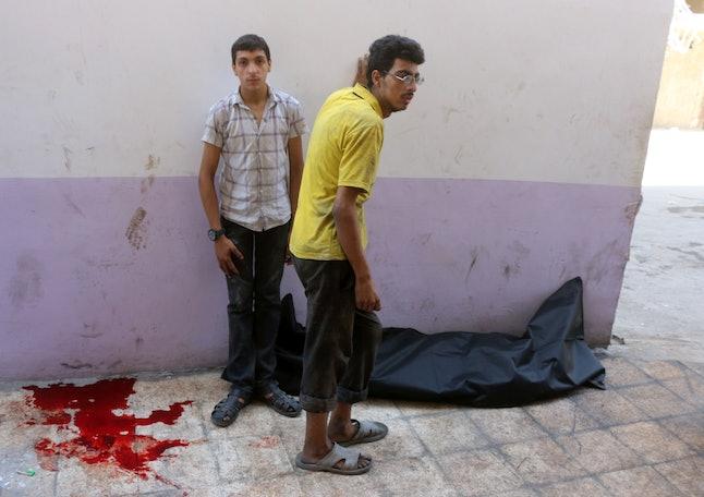 Blood pools near a body bag at a makeshift hospital in the Tariq al-Bab neighborhood of Aleppo, Aug. 16.