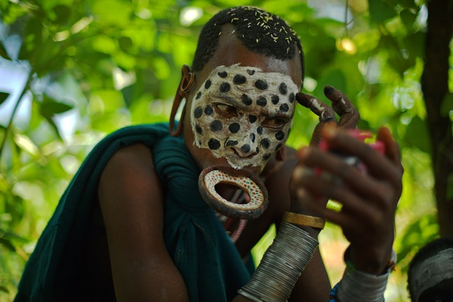 A woman from the Suri tribe wearing a lip plate paints her face in Ethiopia's southern Omo Valley region near Kibbish on September 25, 2016.