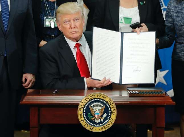 President Donald Trump signs an immigration executive order, January 2017.