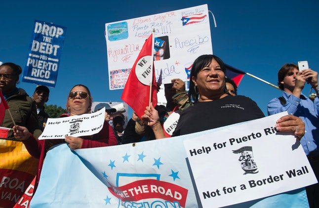 Demonstrators hold a protest to demand more recovery assistance for areas hit by recent hurricanes, including Puerto Rico.