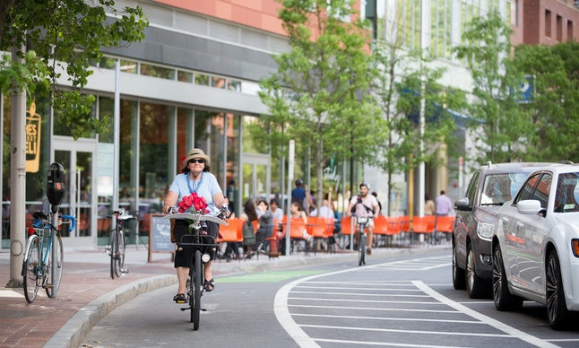A woman rides a bike in a bicycle lane in Cambridge, Massachusetts, where about 24% of people walk to work and 7.2% bike, according to the 2014 American Community Survey.