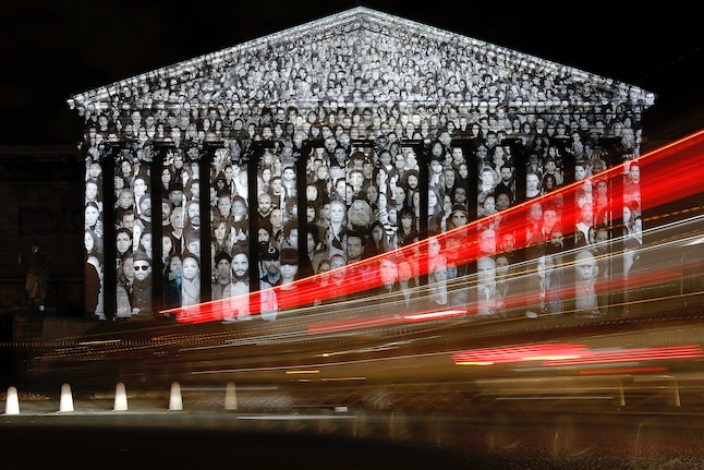Cars pass by the national assembly in Paris, where a projection of French artist JR is displayed as part of the 2015 Paris Climate Conference.