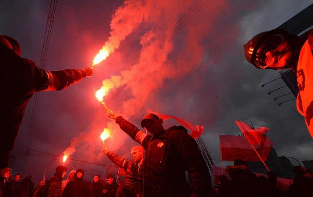 Demonstrators burn flares and wave Polish flags during the annual march to commemorate Poland's National Independence Day in Warsaw, Poland, on Nov. 11.