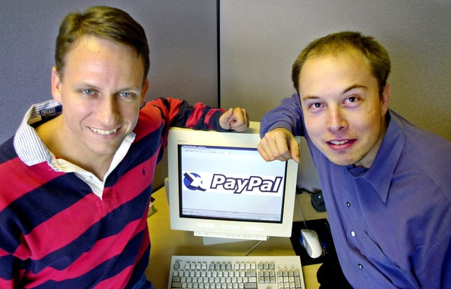 In Oct. 20, 2000, PayPal then-CEO Peter Thiel, left, and founder Elon Musk, right, pose with the PayPal logo at corporate headquarters in Palo Alto, California.