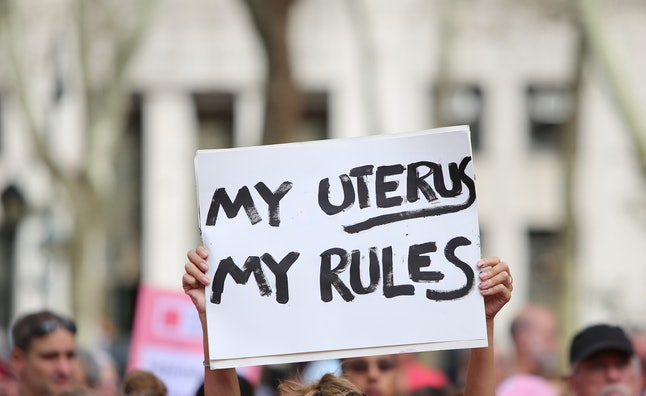 "A pro-choice protester holds up a placard that reads, ""My uterus, my rules."""