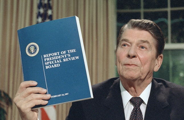 President Ronald Reagan holds up a copy of the Tower Commission report on the Iran-Contra affair on Aug. 13, 1987.