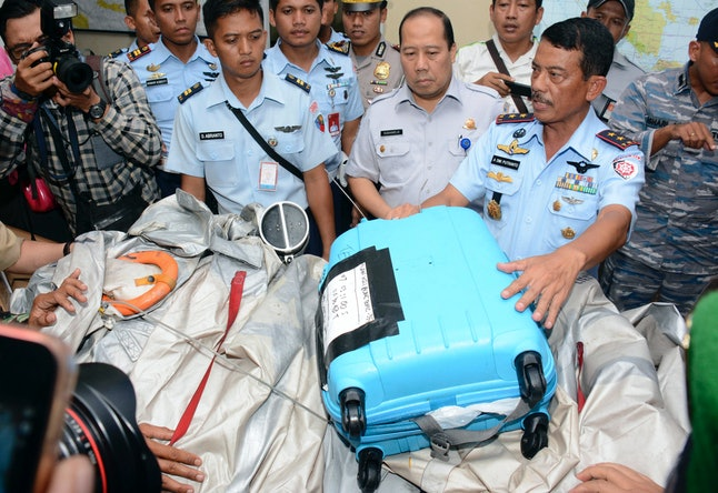 Commander of Indonesian Air Force 1st Operational Command Rear Marshall Dwi Putranto, center, shows the airplane parts and a suitcase found floating on the water near the site where AirAsia Flight 8501 disappeared, during a press conference at the airbase in Pangkalan Bun, Central Borneo, Indonesia, Tuesday, Dec. 30, 2014.