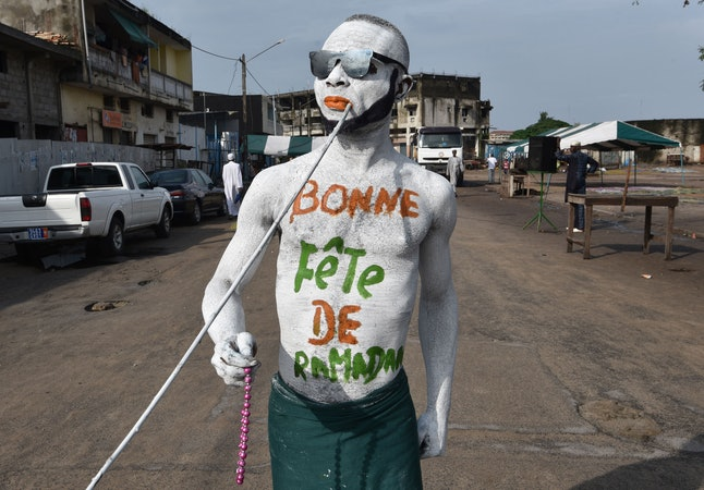A man wearing makeup reading 'Happy Ramadan' walks through the streets of Abidjan, West Africa.