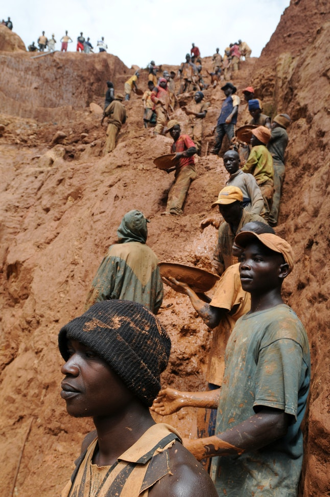 Workers on the muddy cliff of a gold mine in north eastern Congo, Africa.