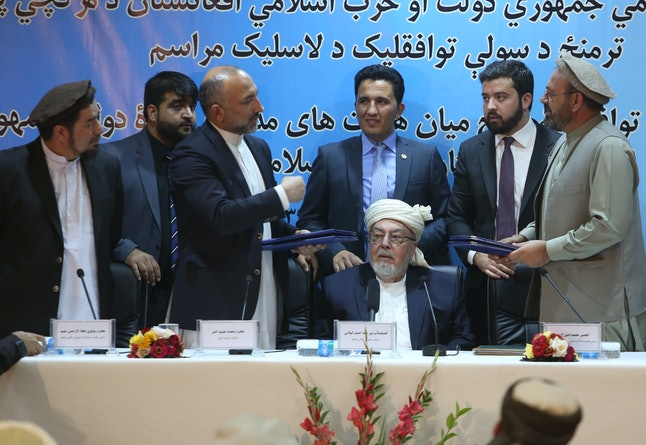 Representatives of Gulbuddin Hekmatyar and the Afghan government sign a peace deal Thursday in Kabul.