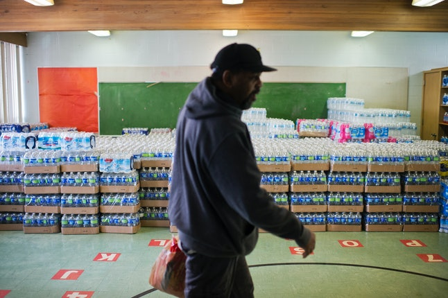 A volunteer walks by cases of bottled water at the St. Mark's Baptist Church in Flint, Michigan, in February