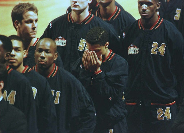 Denver Nuggets guard Mahmoud Abdul-Rauf (C) bows his head in prayer March 15, 1996, in Chicago, Illinois, during the singing of the national anthem before playing the Chicago Bulls.