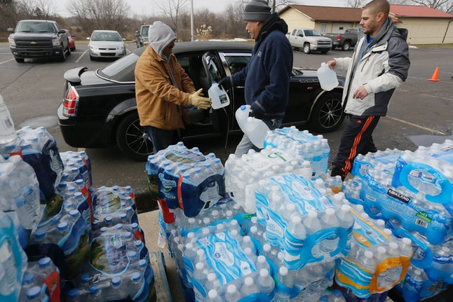 In a Feb. 5, 2016 file photo, volunteers load a vehicle with bottled water at Our Lady of Guadalupe Church, in Flint, Michigan.
