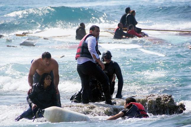 Greek army Sgt. Antonis Deligiorgis helps an Eritrean migrant.