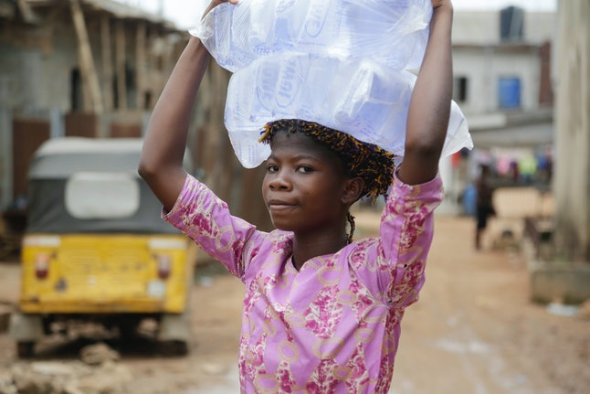 A woman carries a bag of water in Lagos, Nigeria