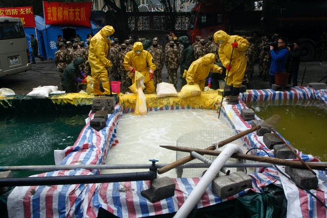 Chinese firefighters diluting a river polluted with cadmium.