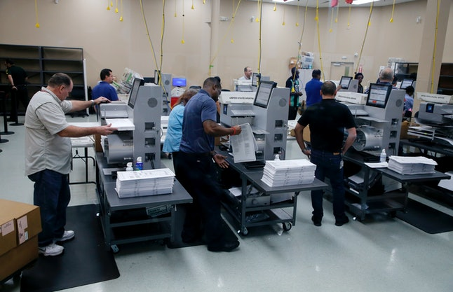 Elections staff load ballots into machines as recounting begins Sunday at the Broward County Supervisor of Elections Office in Lauderhill, Florida.