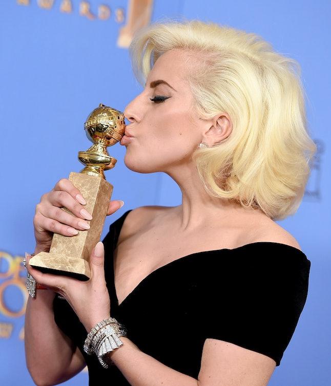 Lady Gaga kissing her golden globe