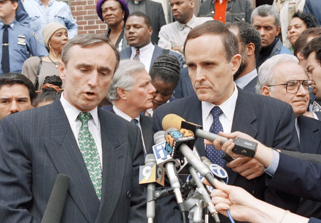 New York City Police Commissioner William Bratton, left, makes an appeal for calm at a news conference held outside Borough Hall in the Staten Island section of New York as New York City Mayor Rudolph Giuliani looks, April 30, 1994.