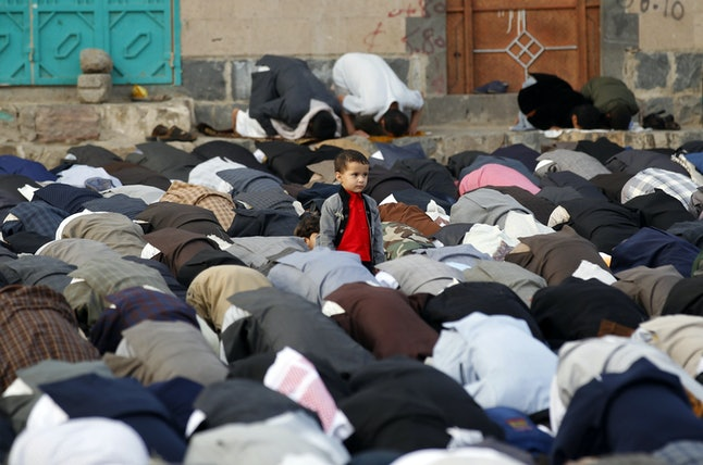 A Yemeni boy stands among Muslim worshippers performing Eid al-Fitr prayers at a square in the capital of Sanaa.