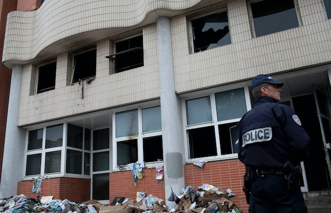 """In this file photo dated Wednesday, Nov. 2, 2011, a police officer stands front of the headquarters of satiric French newspaper Charlie Hebdo, that """"invited"""" the Prophet Muhammad as a guest editor this week, in Paris. A gun assault on the Paris offices of satirical magazine Charlie Hebdo on Wednesday Jan. 7, 2014, was the deadliest terrorist attack in France's recent history, and joins the roll of various terror attacks in western Europe, including the 2011 firebombing of the offices of Charlie Hebdo after the satirical magazine runs a cover featuring a caricature of the Prophet Muhammad. No one is injured in the 2011 arson attack."""