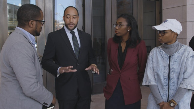 Glo Merriweather, far right, looks on as their attorneys, Darlene Kannady and Mark Simmons Jr., center, talk about Merriweather's Nov. 28 arraignment.